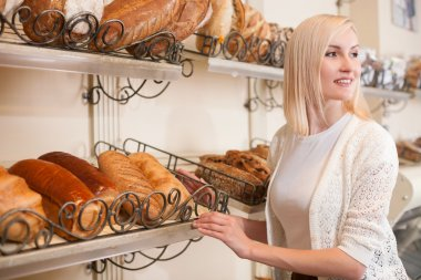 Skillful saleswoman is serving customers in bakery