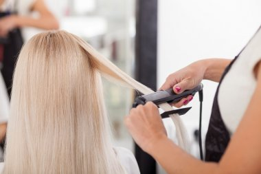 Professional hairstylist is working with iron straightener
