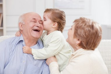 Cute small child is expressing love to grandparents