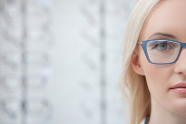 Cheerful young lady is wearing new eyeglasses