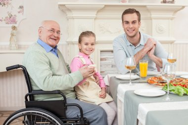 Cheerful old disabled grandfather with his family