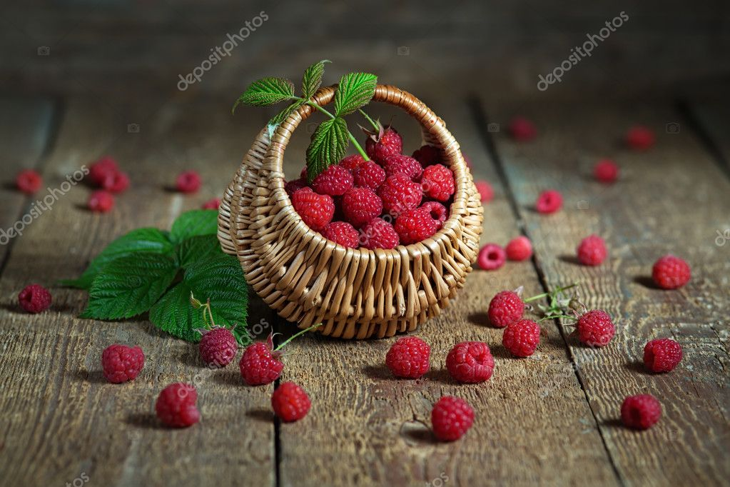 Ripe raspberry in a basket on wooden table