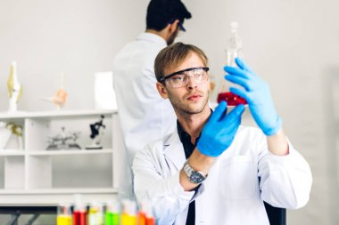Professional two scientist man research and working doing a chemical experiment while making analyzing and mixing liquid in test tube.Young science man dropping sample chemical on glass at laboratory