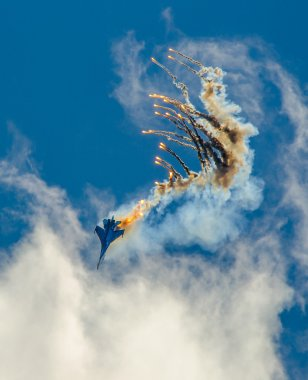 Military aircraft fighter SU-27 nose-dive, performs the maneuver with the ejection of heat missiles, releasing a plume of hot gases.