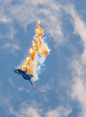 Military aircraft fighter SU-27 performs the maneuver with the ejection of heat missiles, releasing a plume of hot gases.