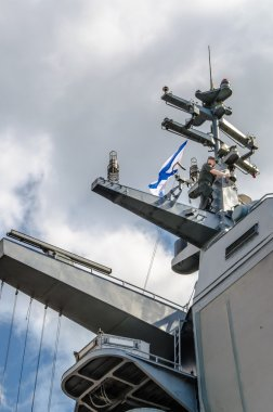 Military naval officer runs high on the mast of a warship on a background of clouds