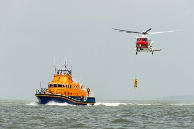 Orange sea rescue life boat with rescue helicopter