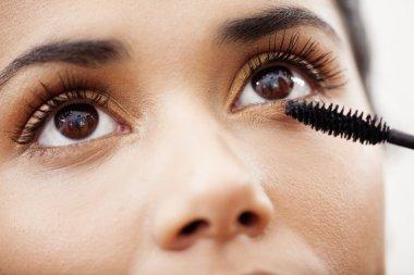 woman putting on mascara