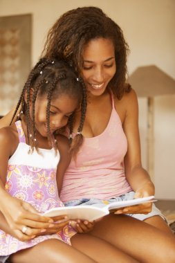 Mother and girl reading book
