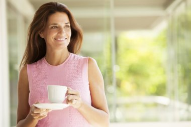 Mature woman holding cup