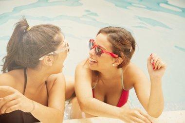Women posing by poolside