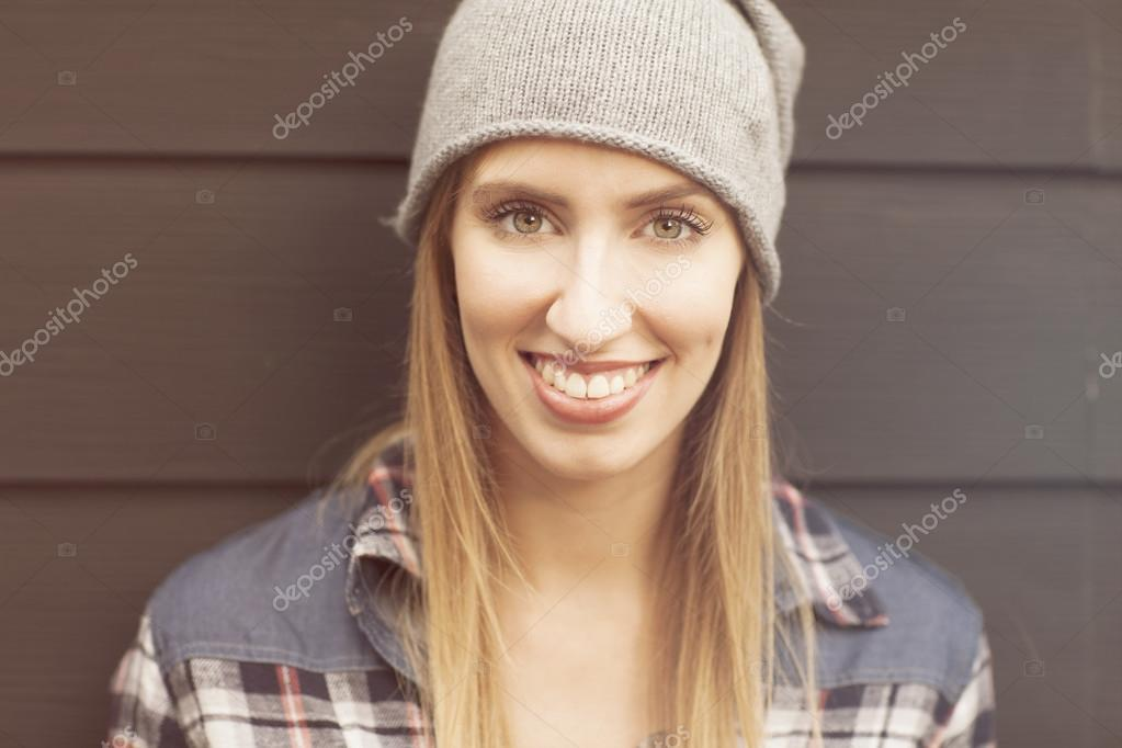 Girl wearing checkered shirt and hat outdoors