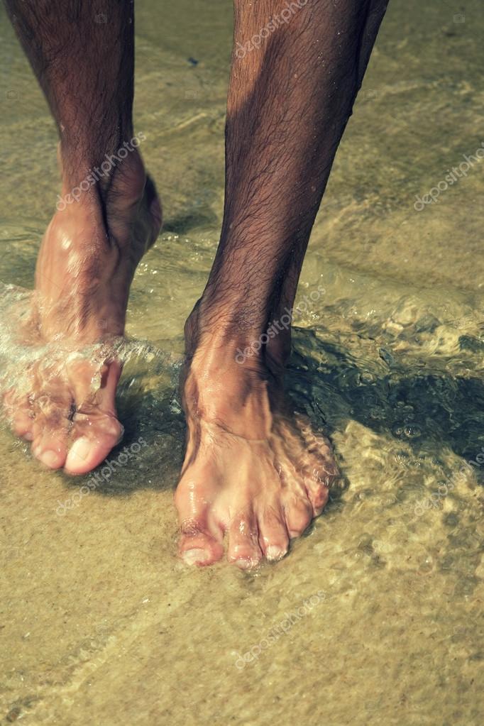 male  feet on the beach