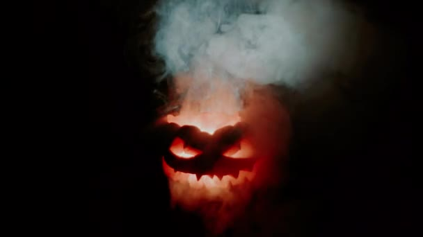 The horrible pumpkin explodes, smoke drifting from his eyes. The flame goes out and then ignites again. Spectacular frightening view. Traditional Halloween holiday decoration shining in the darkness.