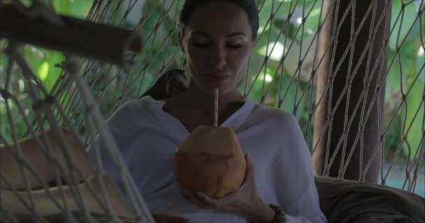 Nő ül függőágyban, és iszik friss fiatal kókusz.Nyári nyaralás koncepció