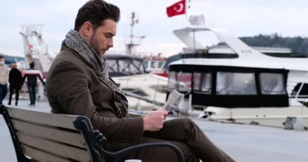 üzletember újságot olvas, miközben ül a padon, olvassa a világ hírei.Bebek