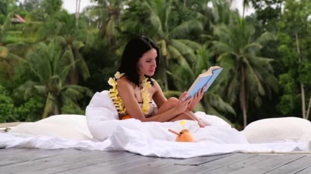 Sexy schöne Frau versteckt sich hinter Palmblättern mit Kokosnuss, Bali Indonesien