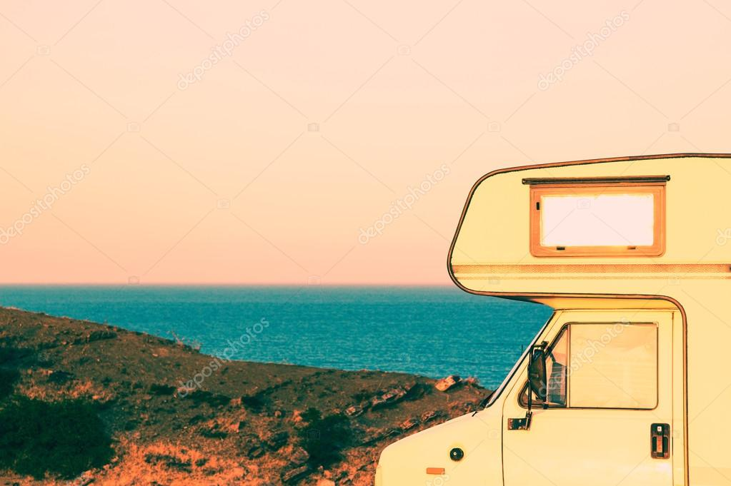 Part of camper on the seashore at sunset