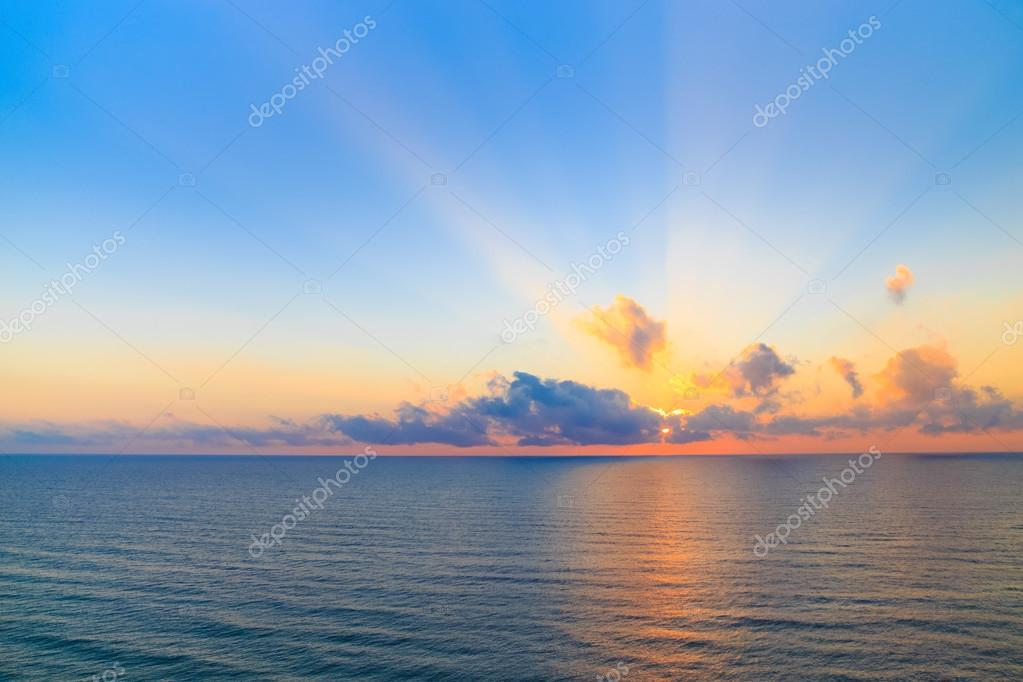 Sunset casting beams of light into the air