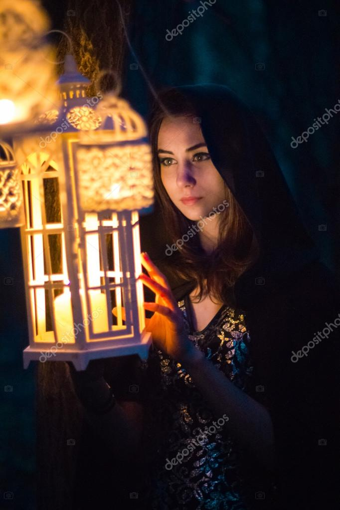 girl with a lantern at night in the forest