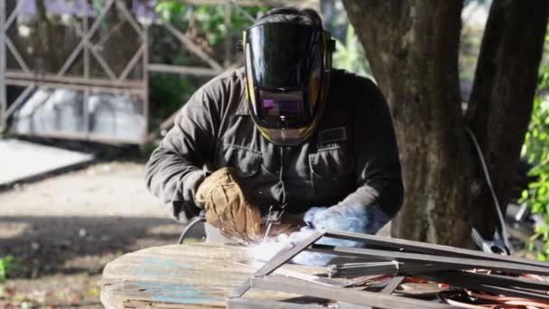 Muž svařování nějaké železo na dřevěném stole, chráněné maskou a rukavicemi, ve venkovním prostoru se stromy, slunečný den