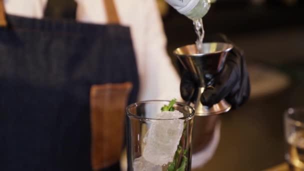 Barkeeper bereitet an der Theke einen Cocktail zu. Indem man alkoholisches Getränk aus einer Flasche in einen kleinen Messbecher aus Metall gießt und dann in einen Glasbecher mit Eis darin. Nahaufnahme an seinen Händen mit schwarzen Handschuhen.