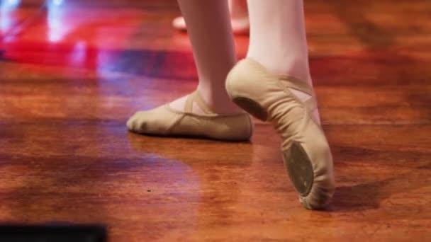 Pohled na nohy dívky baletní tanečnice s její baletní boty trénink na dřevěném jevišti. Opakování kroků baletu.