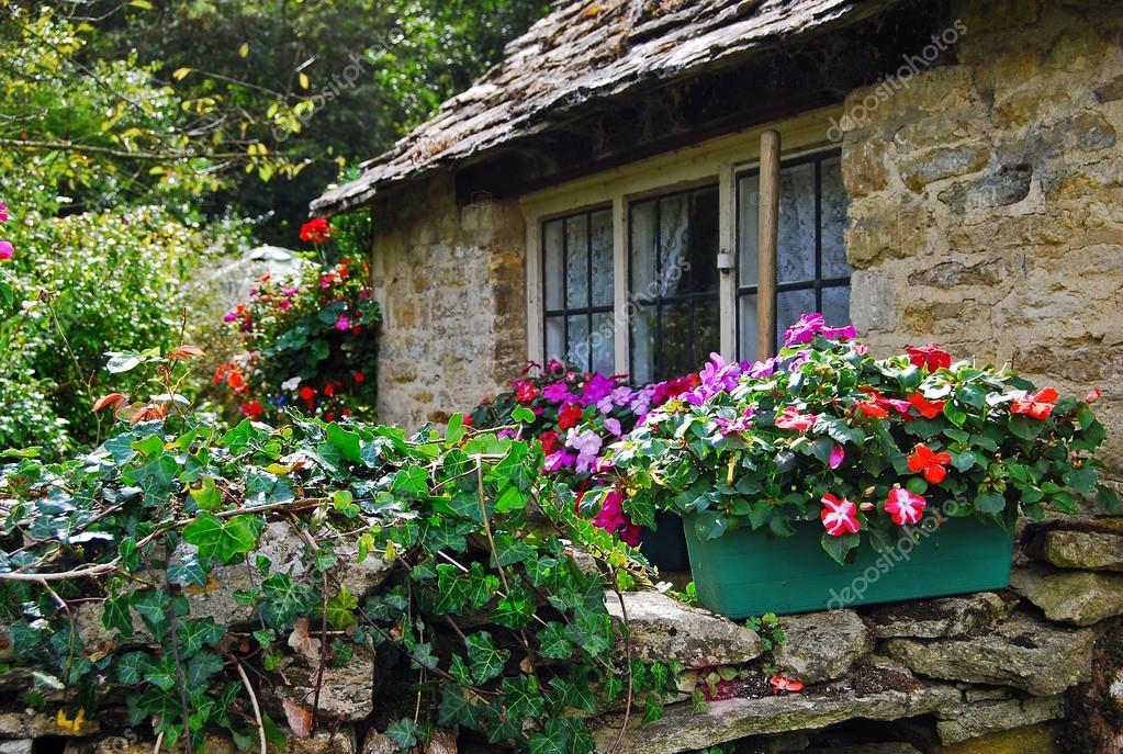 Parete di pietra con i fiori di cottage rurale in for Piani di costruzione di cottage gratuiti