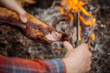 Man carving grilled rabbit meat in forest camp.  Top view.