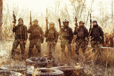 Group of soldiers standing with arms and looking at the camera