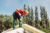 Dachdecker befestigt mit einem Bohrer eine Kappe auf einem Hausdach