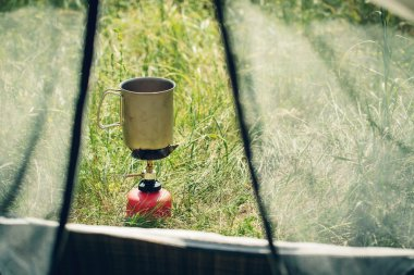 boiling water in mug on portable camping stove