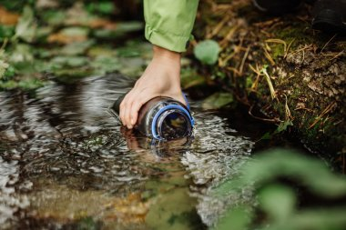woman taking water from forest spring on hiking trip