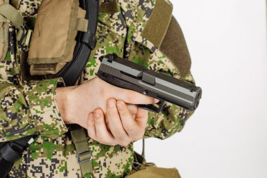 Soldier holding a black handgun. Training of soldiers firing wea