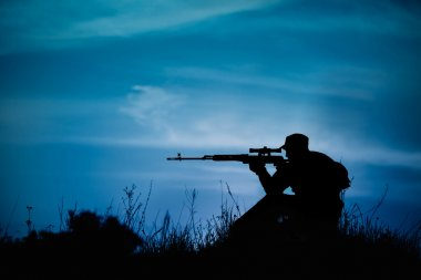 Silhouette of military sniper with weapons at night.