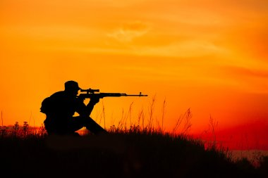 Silhouette of military sniper with sniper rifle at sunset. shot,