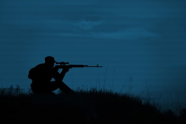 Silhouette of military sniper with sniper rifle at night. shot,