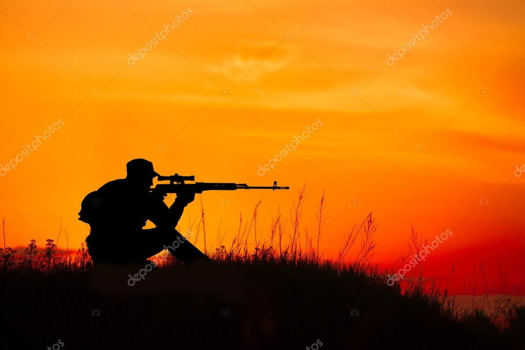Silhouette of military sniper with sniper rifle at sunset ...
