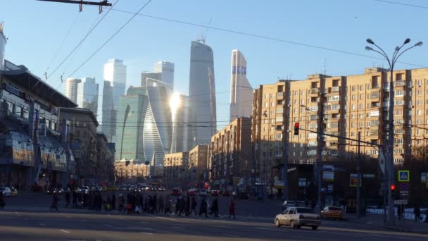 Crowd of People is Walking Across The Road in Moscow Traffic Lights Cars Stop Modern Buildings are on a Horizon Spiral Building Skyscrapers Blue Sky