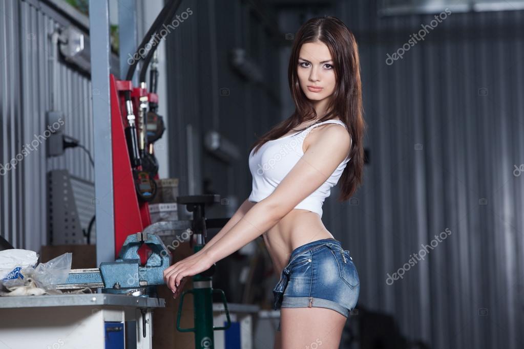 Girl in car repair garage