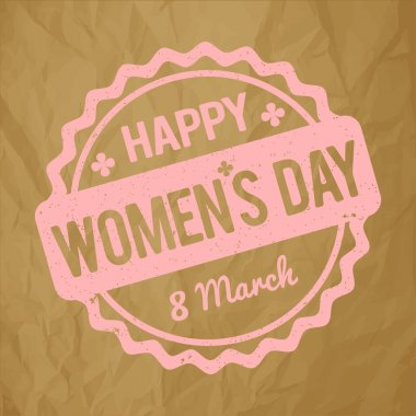 Happy Women's Day rubber stamp pink on a crumpled paper brown background.