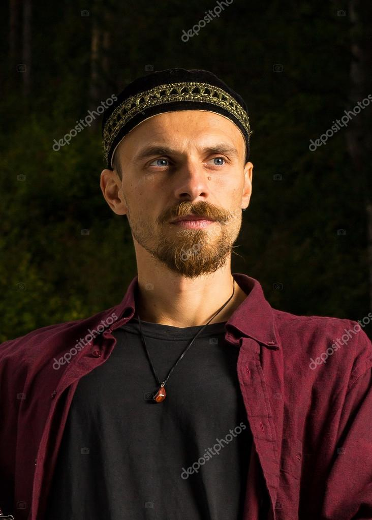A portrait of a young handsome man with blue eyes, central asia style tubeteika cap and a karneol pendant