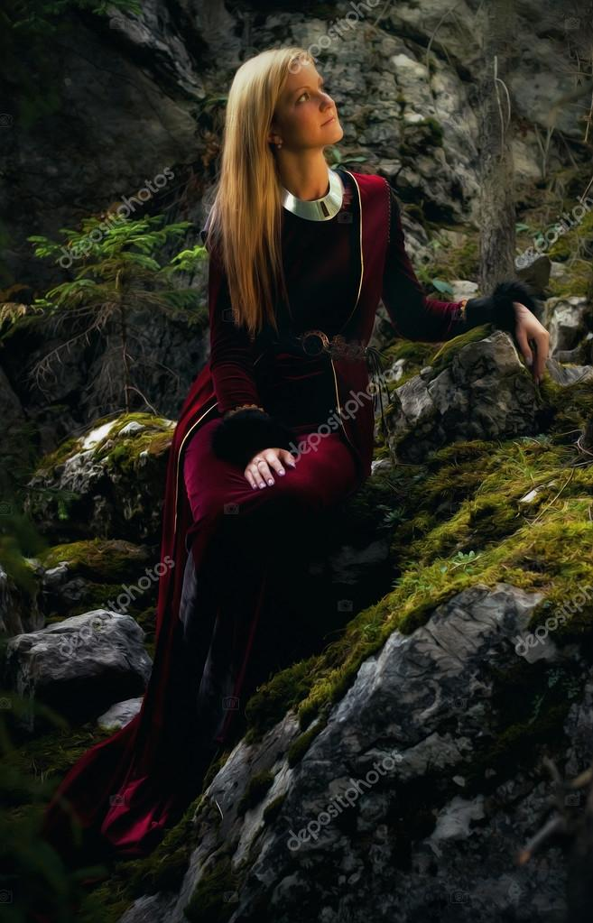 beautiful woman fairy with long blonde hair in a historical gown is sitting amids moos covered rocks in enchanting forestral landscape