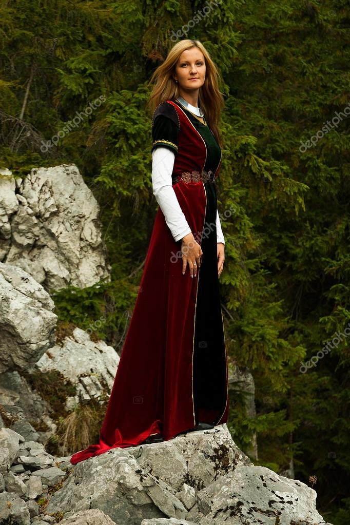 beautiful woman fairy with long blonde hair in a historical gown is standing on rocks amids a breathtaking  forestral landscape