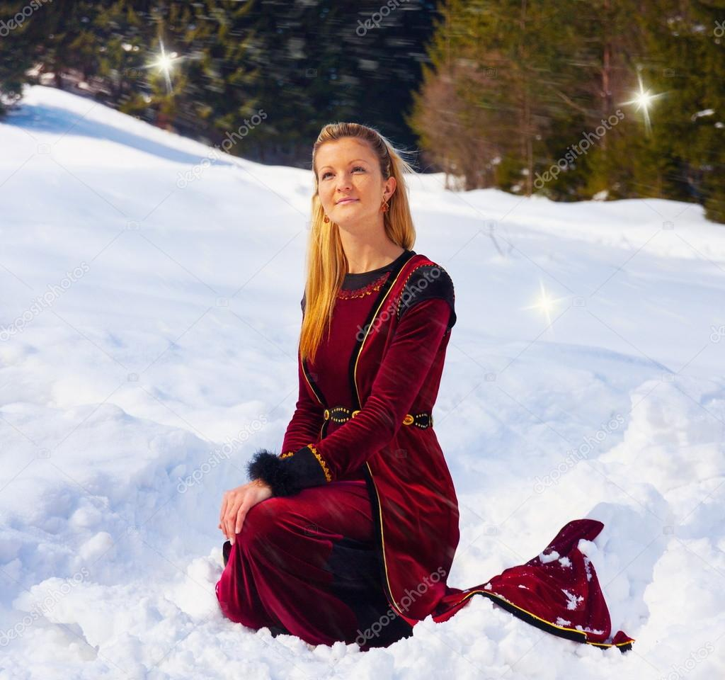 A beautiful young blonde lady in medieval velvet clothing posing in the snowy mountain landscape with fairy starlights