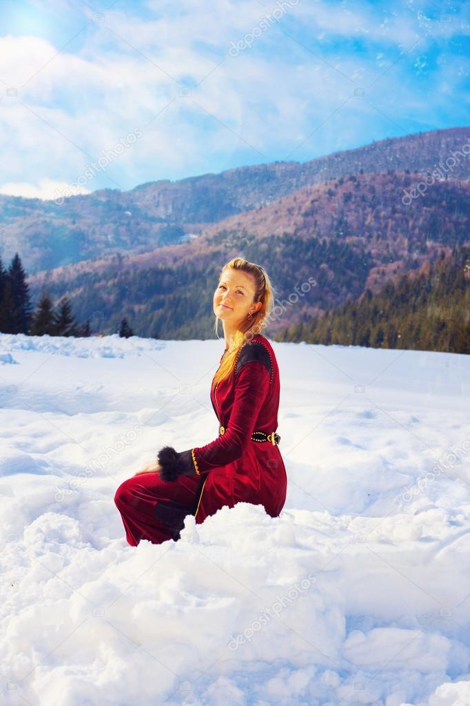 A beautiful young blonde lady in medieval velvet clothing posing in the snowy mountain landscape