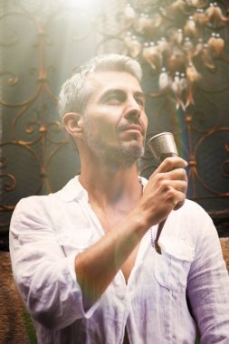 Sexi Man in a white shirt and medieval mead horn in hand. Toast concept. Ornamental window on background, and Dream Catcher. in sun light