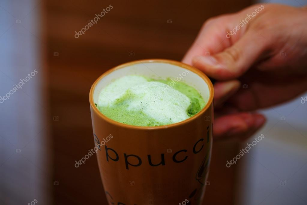 Mixing Green Barley Grass Powder in man hand. Juice for Vitality a Health