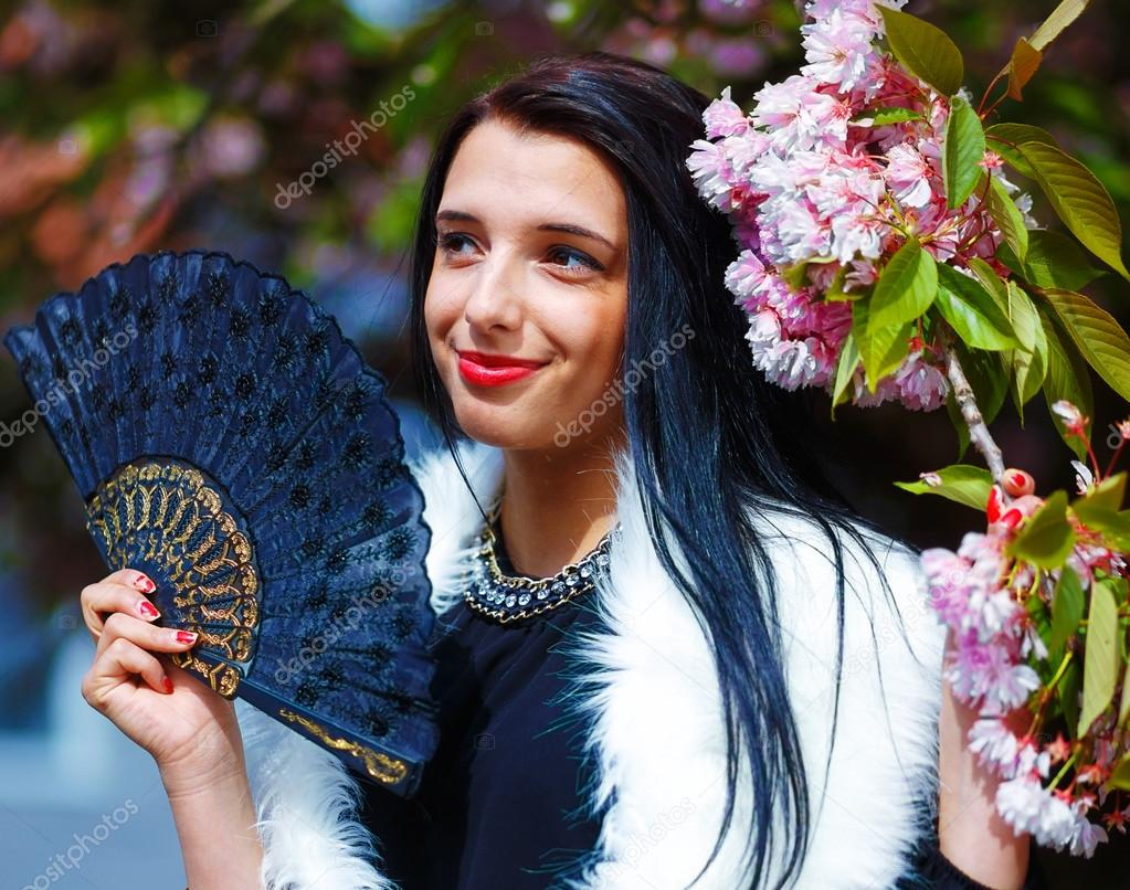 Beautiful woman with flowers glamour white fur and black fan in beautiful woman with flowers glamour white fur and black fan in hand posing next izmirmasajfo