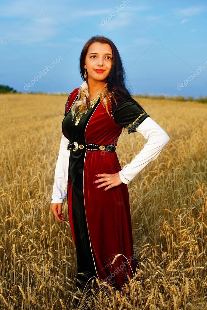 Smiling Young woman with medieval dress standing on a wheat field with sunset. Natural background.